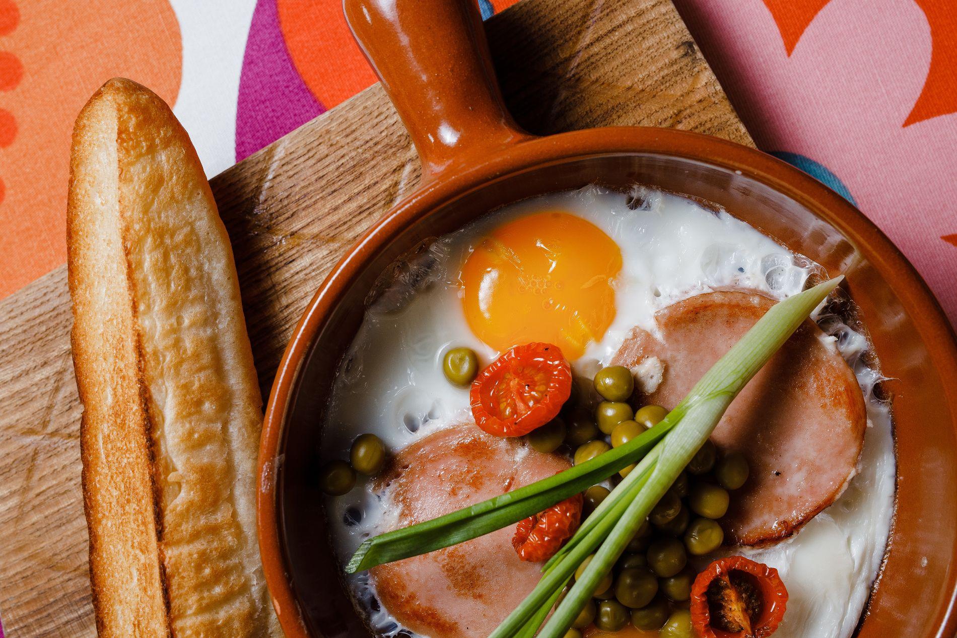 Яичница-глазунья с докторской колбасой, горошком, хлебом и луком ©Фотография предоставлена рестораном «Пиноккио Djan»