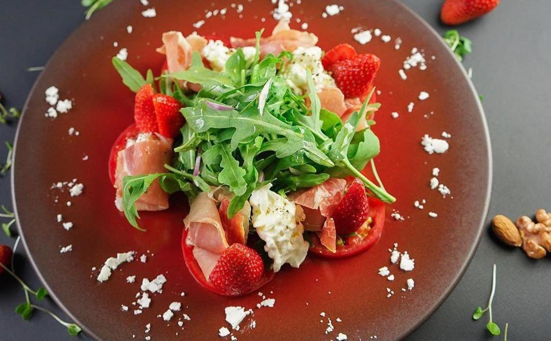 Салат с пармой, клубникой и сыром страчателла ©Фото со страницы ресторана «Ателье вкуса» в инстаграме