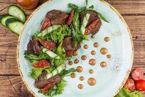 Телятина су-вид с вялеными томатами, листьями салата, рукколой и овощами © Фото со страницы кафе «МэниПельмени» в инстаграме www.instagram.com/manypelmeni