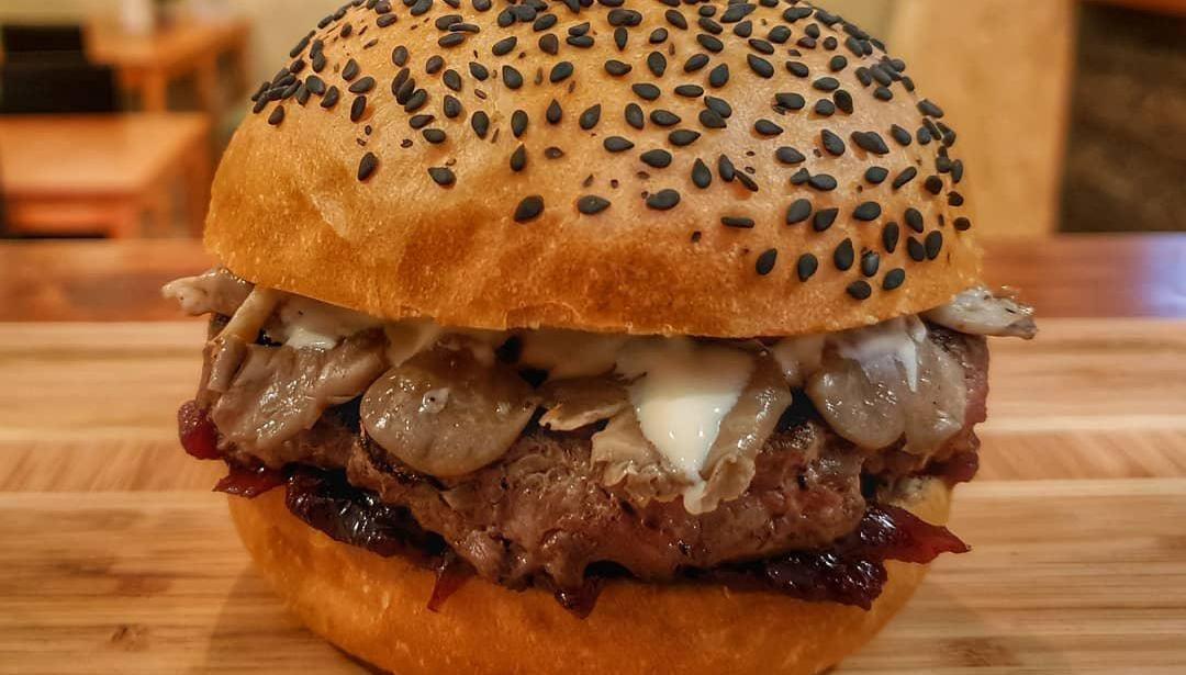 Бургер с котлетой из мяса Black Angus, маринованными вешенками, луковым мармеладом и сливочным соусом